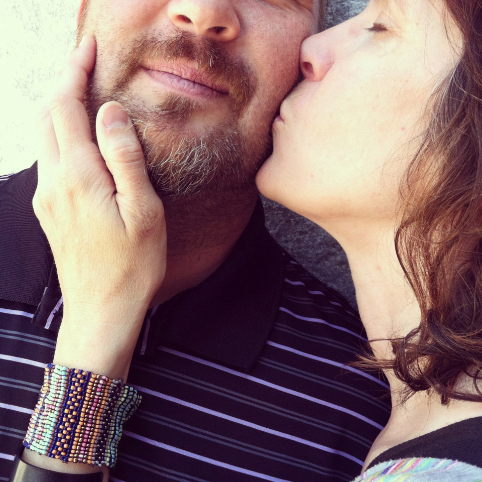 woman kissing the scratchy cheek of a bearded man