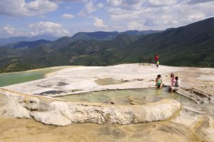 Mexico, Oaxaca, Hierve el Agua, Tourists beside limestone pools and looking out over surrounding countryside. (Photo by: Eye Ubiquitous/UIG via Getty Images)